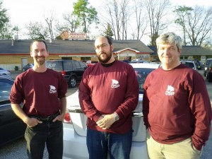 Three team members wearing their maroon OSP team shirts, standing in the parking lot of Squealer's restaurant