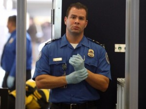 A TSA agent adjusts his light blue vinyl examination gloves