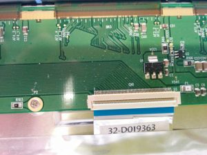 This delicate ribbon cable emerges from metallic tape and connects to a tab on the top edge of the back of the monitor.