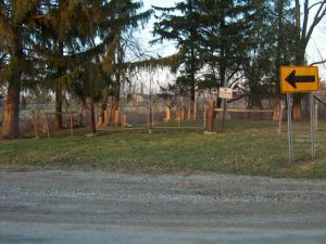 The view of the cemetery from the road. A metal fence runs in front of the cemetery, and there is a no trespasssing sign near the entrance. Behind the fence a few graves and some trees are visible.