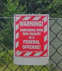Red and white sign that reads: warning! Tampering this facility is a federal offense. US Code Title 42, Section 3*** (the section is blurry). Below that, it says to report suspicious activity to... but does not provide contact information