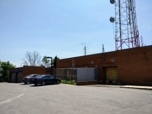 Singe level brick building with WWPB TV logo; above the building, a large commercial mast supporting a lot of antennas.